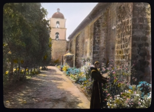 Friar in the garden courtyard, Mission Santa Barbara, 1917